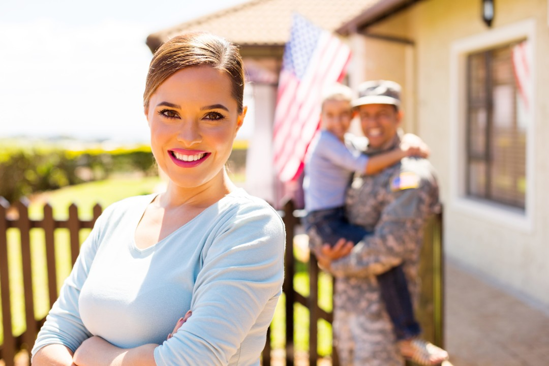 Military Spouse in Front of Home with Military Family-min