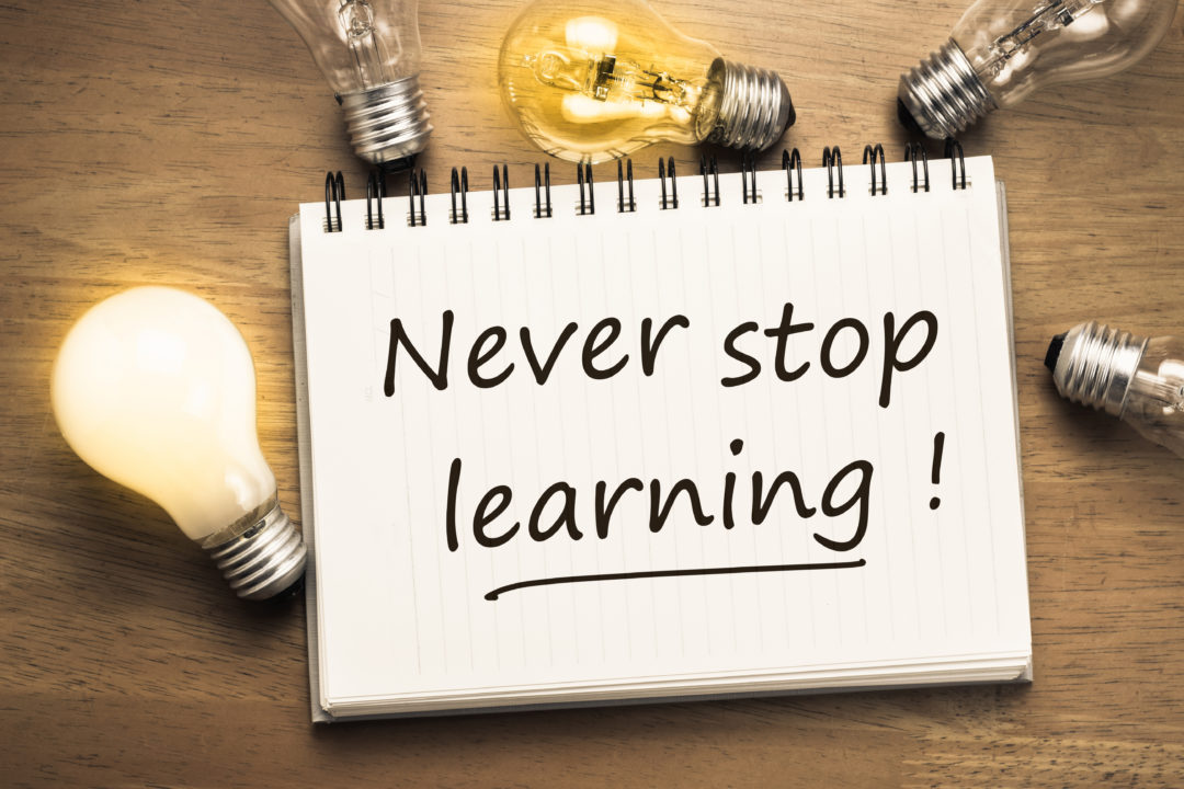 Never Stop Learning, handwriting quotation on notebook with light bulbs